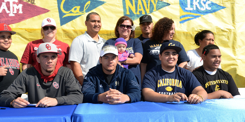 Description of . Football players, from left, Dallis Todd, Oklahoma, Tyler Luatua, Notre Dame, Michael Trani, Cal, and Nofo Ti'i, Navy, appear with their families during National Signing Day at La Mirada High School on Wednesday February 5, 2014. (Staff Photo by Keith Durflinger/Whittier Daily News)