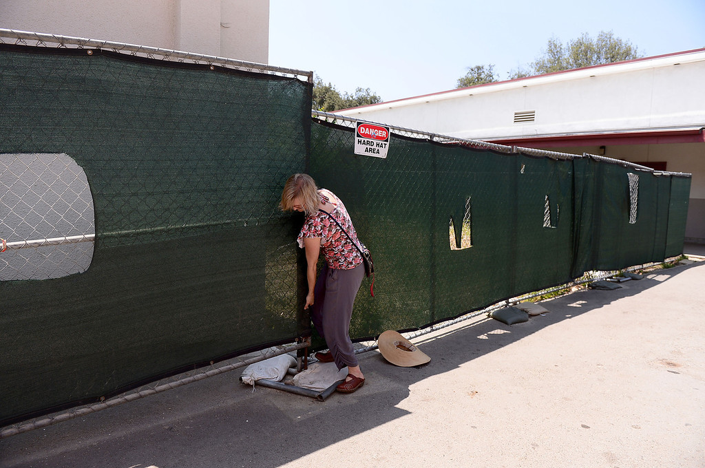 Description of . Biology teacher Joan Stevens, who is trying to save the permaculture garden she cultivated at Arcadia High School from becoming concrete planter boxes as the school modernizes, leaves the garden area Thursday, June 13, 2013 though a construction fence. Stevens is working with district officials to turn the garden into an outdoor classroom.   (SGVN/Staff Photo by Sarah Reingewirtz)
