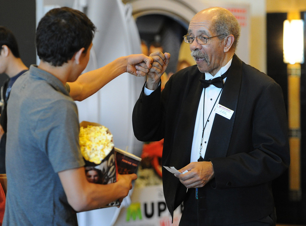 Description of . Al Harris, floor manager of the Krikorian Premier Theatre in Redlands, has become a local icon collecting tickets and giving high fives to moviegoers since being hired in 1992.  (John Valenzuela/Photographer)