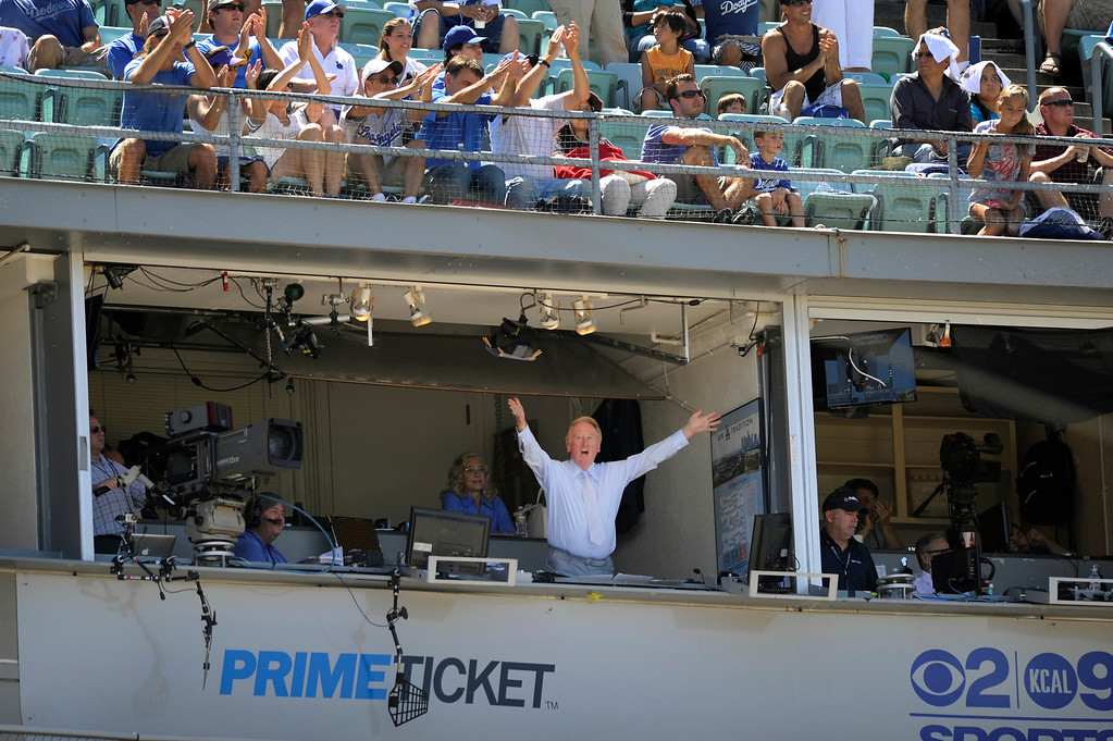 Description of . Dodgers announcer Vin Scully waves to the crowd after it was announced he will return to the booth in 2013. (Michael Owen Baker/L.A. Daily News)