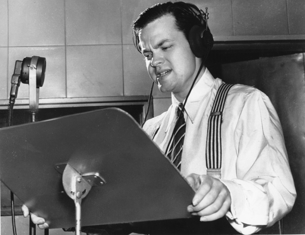 Description of . Orson Welles delivers a radio broadcast from a New York studio in 1938.  On the same year on Oct. 30, he broadcasted the adaptation of H.G. Wells'
