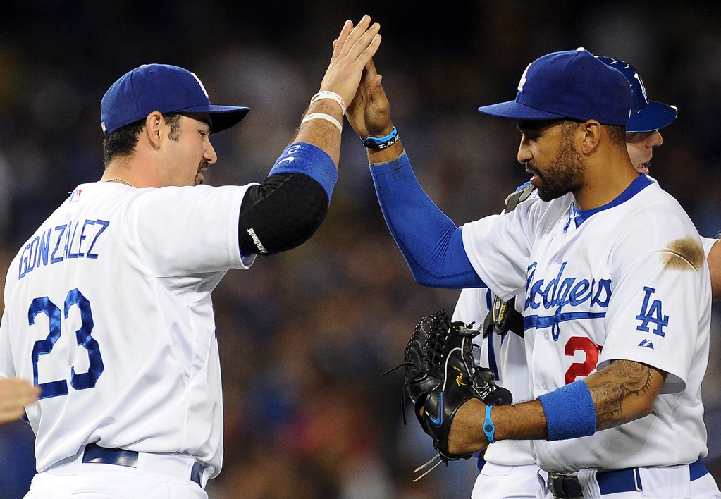 Description of . Los Angeles Dodgers' Matt Kemp, right, high fives first baseman Adrian Gonzalez (23) after defeating the Milwaukee Brewers 7-5 during their baseball game against the Milwaukee Brewers on Friday, April 26, 2013 in Los Angeles.   (Keith Birmingham/Pasadena Star-News)