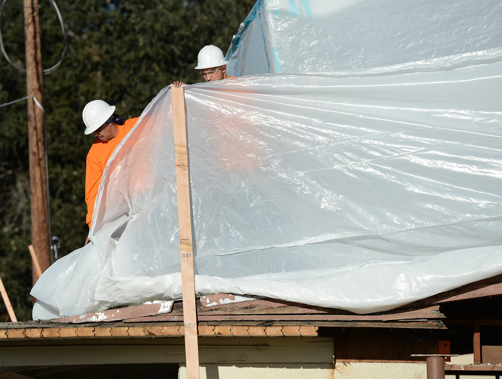 Description of . Workers put up tarps as Asbestos is being removed by Resource Environmental, Inc. from La Habra Heights City Hall on Wednesday January 22, 2014. More asbestos was found in the roofing material last week. (Staff Photo by Keith Durflinger/Pasadena Star-News)
