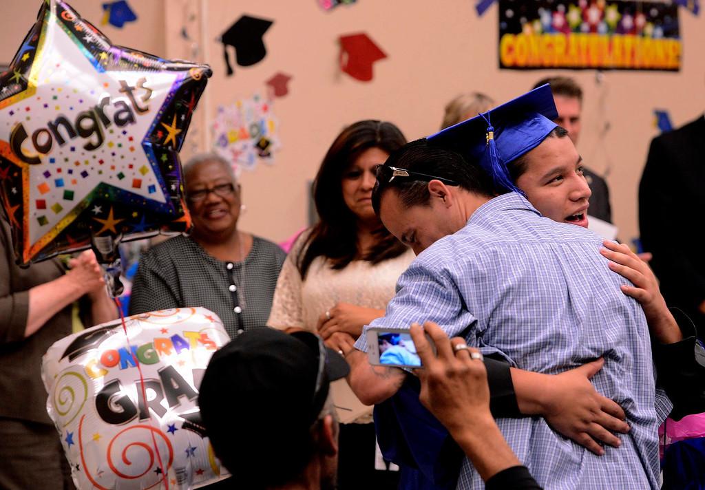 Description of . Graduate Dominic Vasquez, right,  hugs his uncle Paul Gomez during Commencement Ceremonies at Carl And Dora Anderson School in San Bernardino May 21, 2013.  GABRIEL LUIS ACOSTA/STAFF PHOTOGRAPHER.