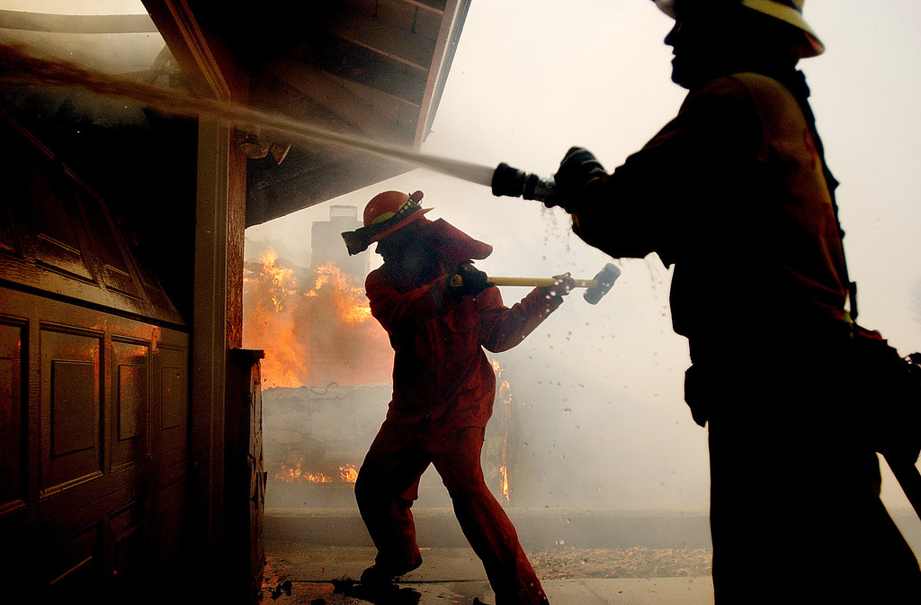 Description of . Ten years ago this month the arson caused Old Fire, fanned by Santa Ana winds burned thousands of acres, destroyed hundreds of homes and caused six deaths. The fire burned homes in San Bernardino, Highland, Cedar Glen, Crestline, Running Springs and Lake Arrowhead and forced the evacuation of thousand of residents.  San Bernardino County Fire Fighter Jacques Plummer, right, sprays water on a home as a inmate fire fighter tries to break down a garage door while fighting the Old Fire in San Bernardino. (Staff file photo/The Sun)