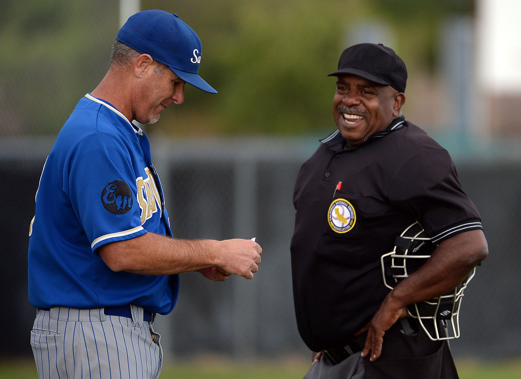 Description of . San Dimas head coach Mike Regan talks with the home plate umpire in the sixth inning of a prep baseball game against Northview at Northview High School in Covina, Calif., on Wednesday, March 26, 2014. San Dimas won 2-0.