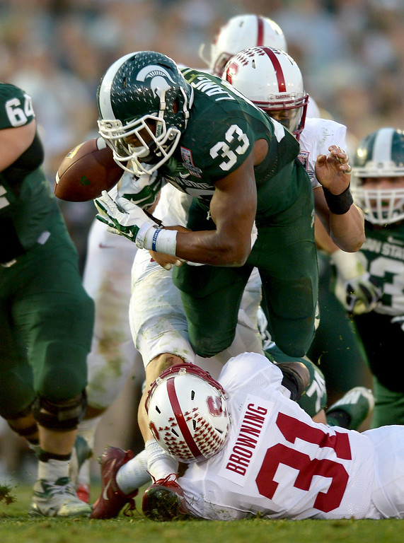 Description of . Michigan State RB Jeremy Langford fumbles after being hit by Stanford's Barry Browning, bottom, and Shayne Skov, back in the third quarter at the Rose Bowl, Wednesday, January 1, 2014. (Photo by Michael Owen Baker/L.A. Daily News)