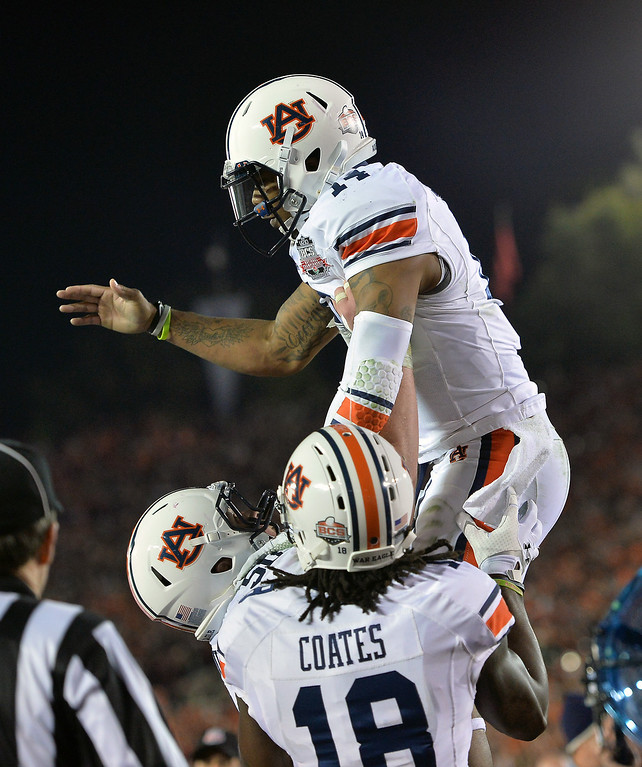 Description of . Auburn QB Nick Marshall is lifted by teammates after his second-quarter touchdown against Florida State at the BCS national championship game at the Rose Bowl, Monday, January 6, 2014. (Photo by Michael Owen Baker/L.A. Daily News)