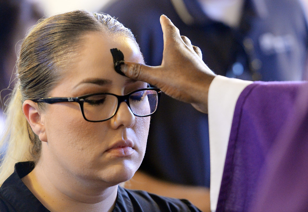 Description of . Parishioners at Our Lady of Carmel Church in Rancho Cucamonga receive ashes on their forehead to mark the beginning of Lent on Ash Wednesday March 5, 2014.  (Will Lester/Inland Valley Daily Bulletin)