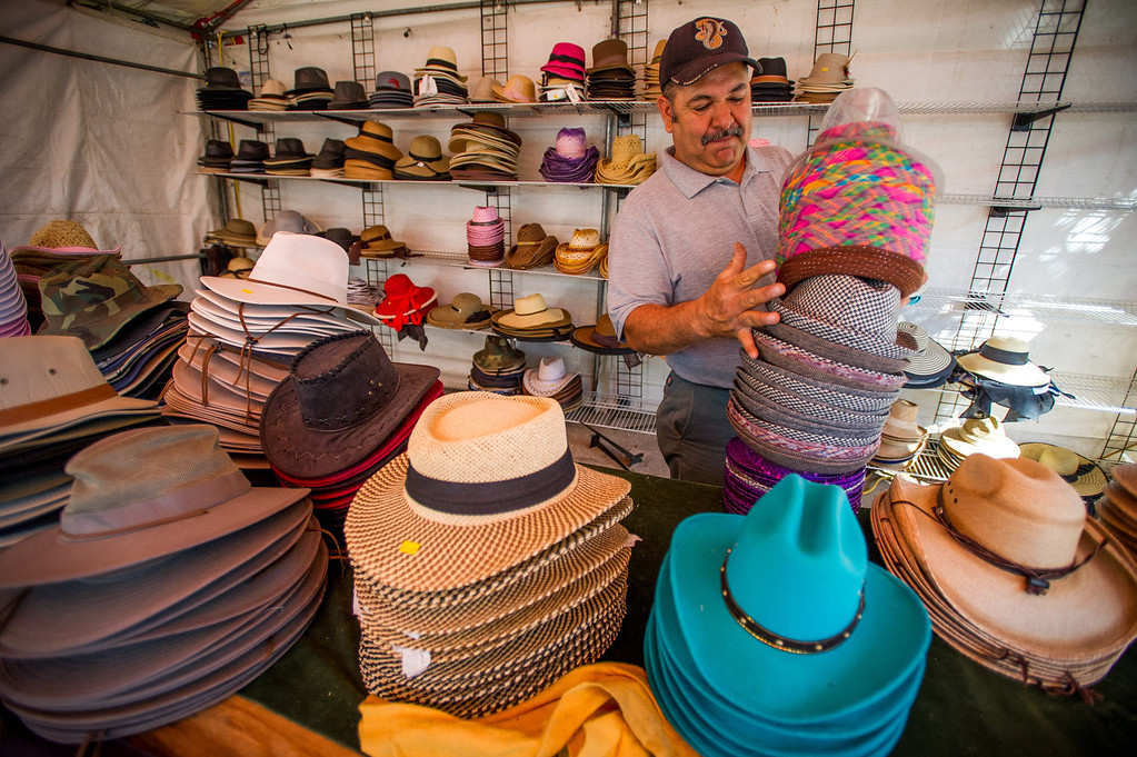 Description of . Chris Munoz of Pomona sets out hats for Mam Imports as preparations are made for opening day of the San Bernardino County Fair in Victorville, Friday,  May 24 2013. (Eric Reed/The Sun)