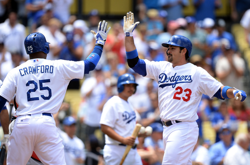 Description of . Adrian Gonzalez #23 of the Los Angeles Dodgers celebrates his two run homerun with Carl Crawford #25 for a 2-0 lead over the St. Louis Cardinals during the first inning at Dodger Stadium on May 26, 2013 in Los Angeles, California.  Cardinals won 5-3   (Photo by Harry How/Getty Images)