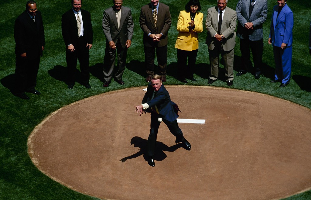 Description of . LOS ANGELES - APRIL 5:  Vin Scully throws out the first pitch on Opening Day before the Los Angeles Dodgers game against the Arizona Diamondbacks at Dodger Stadium on April 5, 1999 in Los Angeles, California. (Photo by Donald Miralle/Getty Images)
