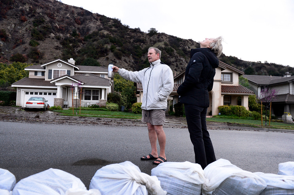 Description of . Dennis and Joann Sanderson walk along their  Ridge View Drive street in Azusa early Saturday morning, March 1, 2014. The Sanderson's stayed behind mandatory evacuation orders. The neighborhood sits below the Colby Fire burn area. (Photo by Sarah Reingewirtz/Pasadena Star-News)