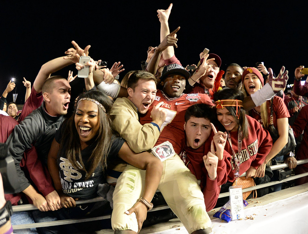 Description of . Florida State wide receiver Levonte Whitfield (7) jumps into the crowd after defeating Auburn 34-31 during the BCS National Championship game at the Rose Bowl in Pasadena, Calif., on Monday, Jan. 6, 2014. 