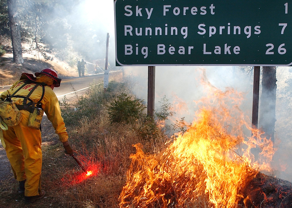 Description of . Ten years ago this month the arson caused Old Fire, fanned by Santa Ana winds burned thousands of acres, destroyed hundreds of homes and caused six deaths. The fire burned homes in San Bernardino, Highland, Cedar Glen, Crestline, Running Springs and Lake Arrowhead and forced the evacuation of thousand of residents. A back fire is lit to burn out the main fire on Highway 18 during the