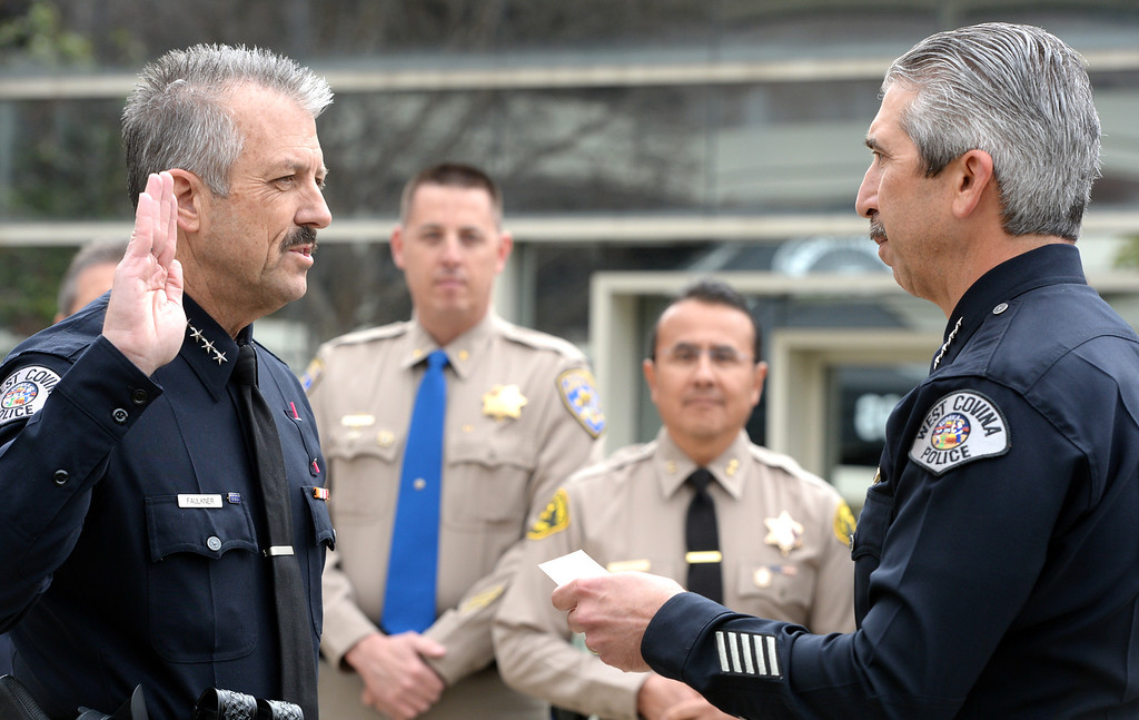 Description of . William Faulkner, left, is sworn in as the new Police Chief by Interim Chief Paul LaCommare, right, during a ceremony at the West Covina Civic Center on Thursday February 6, 2014. Faulkner comes with 30 years of experience after spending much of his career at the Fontana Police Department. (Staff Photo by Keith Durflinger/San Gabriel Valley Tribune)