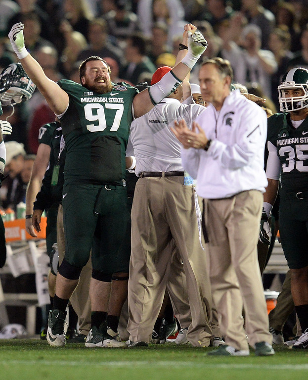Description of . Michigan State's Mark Scarpinato #97 holds his arms in the air as head coach Mark Dantonio claps late in the 4th during the 100th Rose Bowl game in Pasadena Wednesday, January 1, 2014. Michigan State defeated Stanford 24-20. (Photo by Hans Gutknecht/Los Angeles Daily News)