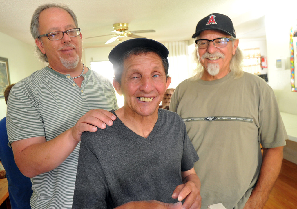 Description of . Gary Borack, 58, is joined by his brothers, Hohn, left, and Robert, right, at his group home in Mission Viejo on Wednesday June 26, 2013. Gary Borack, who was diagnosed with severe mental retardation at the age of 5, recently transitioned out of Lanterman Developmental Center in Pomona about 9 months ago, and is living successfully in the group home. (SGVN/Staff Photo by Keith Durflinger)
