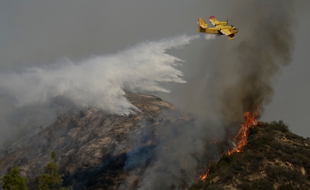 Description of . A super scooper air tanker makes waters drops as  firefighters battle 2,200 plus acre brush fire that started the in early morning in the hills of Glendora Thursday. The fire destroyed six structors and 3 people taken into custody for involvement of starting the fire. Glendora California January 16,2014.