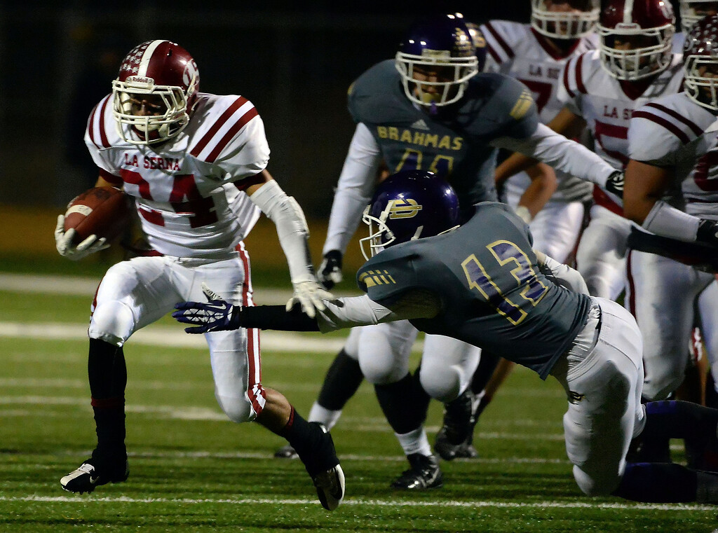 Description of . La Serna's Anthony Garcia (24) runs past Diamond Bar's Chris Torres (13) for a first down in the first half of a CIF-SS playoff football game at Diamond Bar High School in Diamond Bar, Calif., on Friday, Nov. 22, 2013.   (Keith Birmingham Pasadena Star-News)