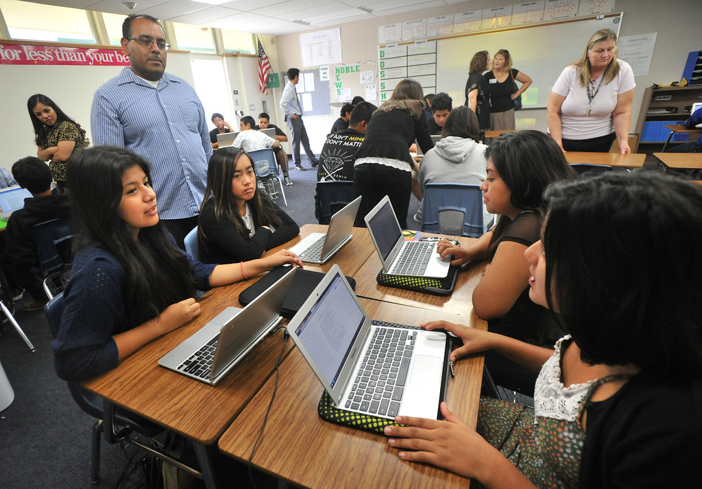 Description of . Students ask questions of biology teacher Miguel Espinoza as they work with their laptops as part of the CORE program at Nogales High School in Rowland Heights on Wednesday September 18, 2013. CORE, the Creation Of Revolutionary Education, is a program that provides a small learning community centered around Technology, Science and English. (San Gabriel Valley Tribune/Staff Photo by Keith Durflinger)