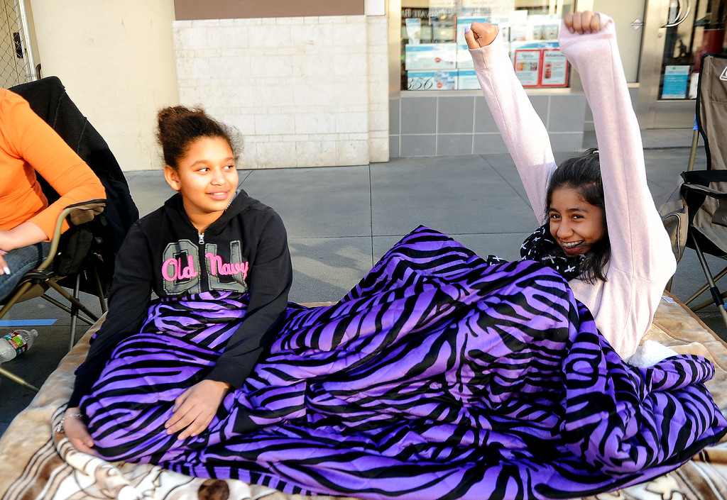 Description of . Eleven-old Dejae Elias, left, of Pasadena shares a laugh with thirteen year-old Monse Elias of San Francisco as they camp out for the Rose Parade along Colorado Boulevard in Pasadena, Calif., on Tuesday, Dec. 29, 2013.     (Keith Birmingham Pasadena Star-News)