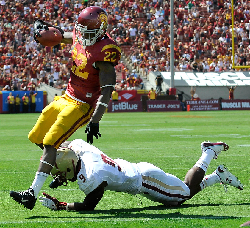 Description of . USC #22 Justin Davis gets past Boston #9 Dominique Williams, on his way to a TD in the 3rd quarter. USC defeated Boston College 35-7 in a game played at the Coliseum in Los Angeles, CA. 9/14/2013. photo by (John McCoy/Los Angeles Daily News)