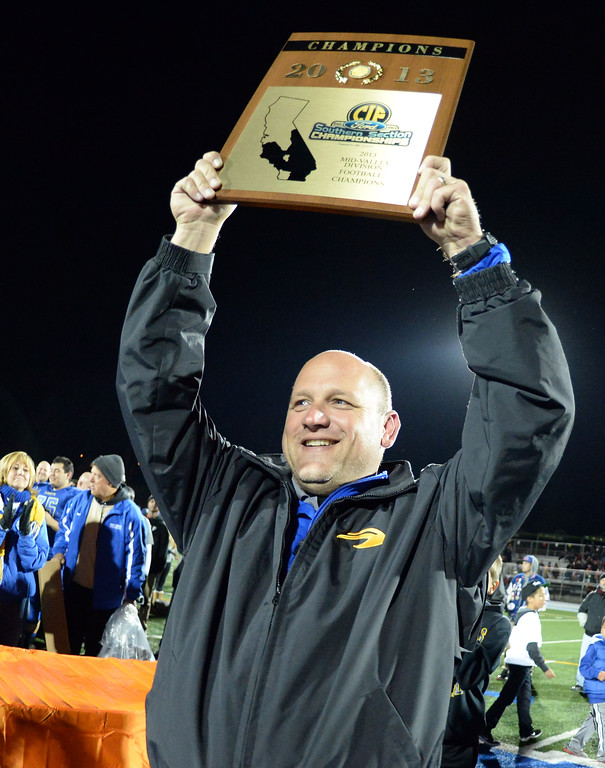 Description of . San Dimas head coach Bill Zernickow holds-up the championship plaque after defeating Paraclete 20-14 a CIF-SS Mid-Valley Division championship football game at San Dimas High School in San Dimas, Calif., on Friday, Dec. 6, 2013.   (Keith Birmingham Pasadena Star-News)