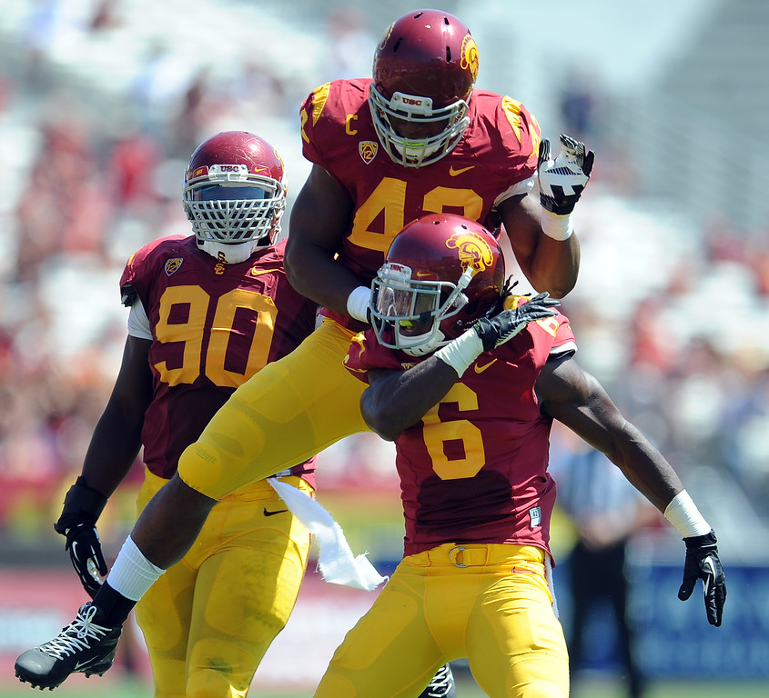 Description of . Southern California's Josh Swah (6) reacts with teammates after after tackling Boston College running back David Dudeck (not pictured) for a loss of yards during the first half of an NCAA college football game in the Los Angeles Memorial Coliseum in Los Angeles, on Saturday, Sept. 14, 2013.