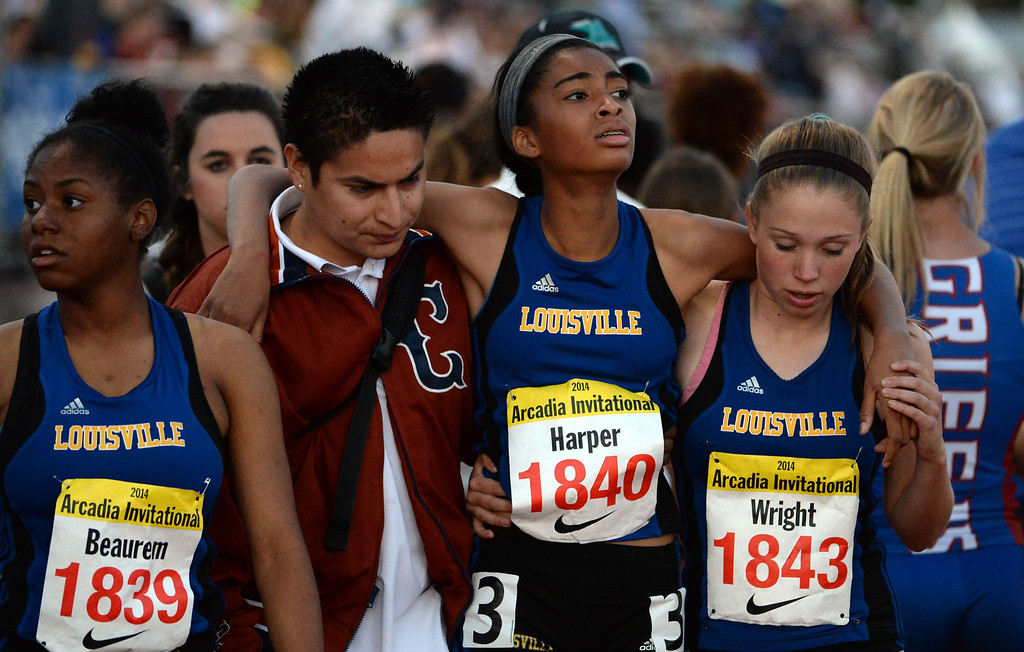 Description of . Louisville's Jayla Harper is helped by teammates after competing in the 800 sprint Medley Invitational during the Arcadia Invitational track and field meet at Arcadia High School in Arcadia, Calif., on Friday, April 11, 2014.  (Keith Birmingham Pasadena Star-News)