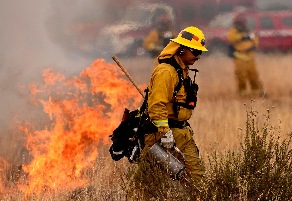 Description of . San Bernardino County firefighter Jeremy Lindsay uses a drip torch during a training fire along Sierra Avenue north of Summit Avenue in North Fontana May 23, 2013.  GABRIEL LUIS ACOSTA/STAFF PHOTOGRAPHER.