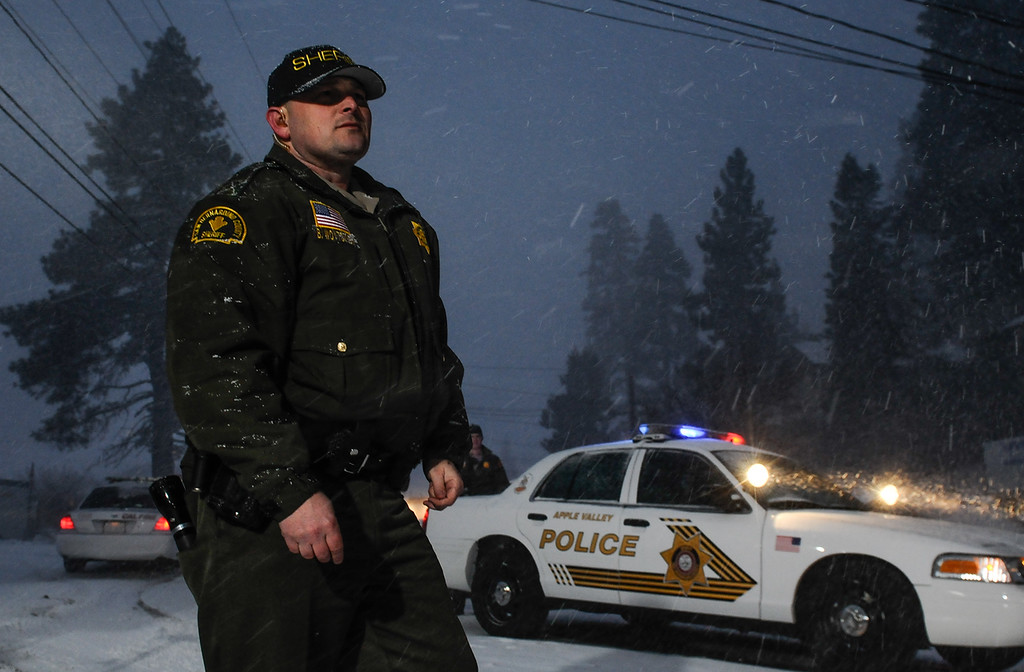 Description of . A deputy monitors a check-point near Bear Mountain Resort during a snow storm early morning as the manhunt for ex-LAPD fugitive Christopher Jordan Dorner in Big Bear on Friday, Feb. 8, 2013. (Staff photo by Rachel Luna/The Sun)