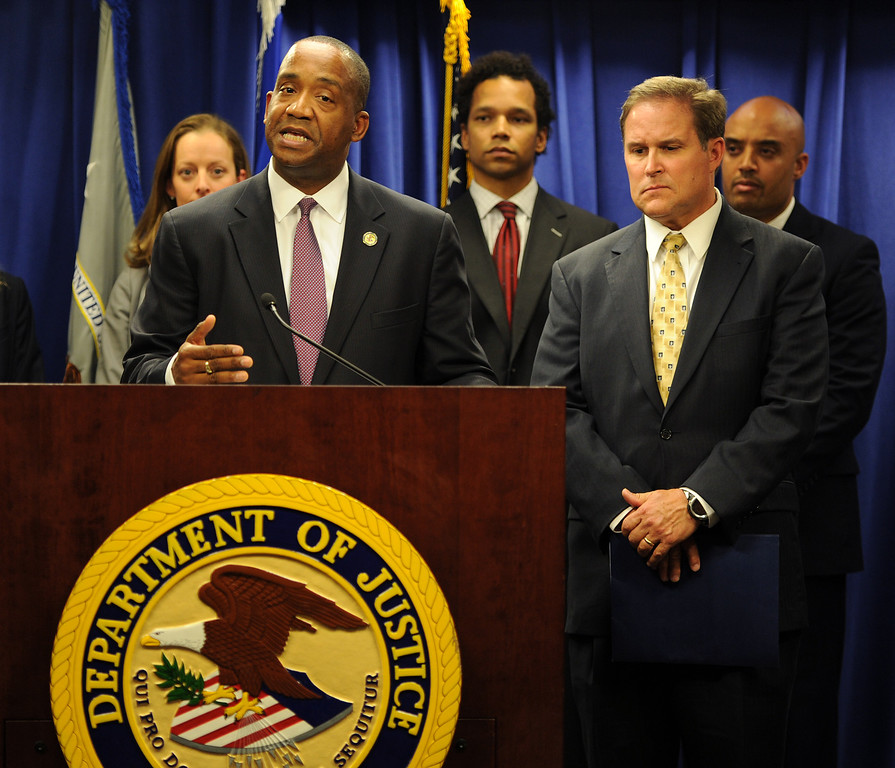 Description of . U.S. Attorney André Birotte Jr., center, and FBI Assistant Director in Charge Bill Lewis stand at the Department of Justice podium in Los Angeles on Friday, Feb. 21, 2014, to announce charges against State Senator Ron Calderon and his brother Tom.that include mail fraud, money laundering, tax evasion, and fraud related to health care. (Photo by John McCoy/Los Angeles Daily News)