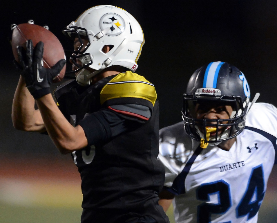 Description of . Bassett's Christopher Rios (13) catches a pass in front of Duarte's Davante Robinson (24) in the first half of a prep football game at Bassett High School in La Puente, Calif., on Friday, Nov. 1, 2013.    (Keith Birmingham Pasadena Star-News)