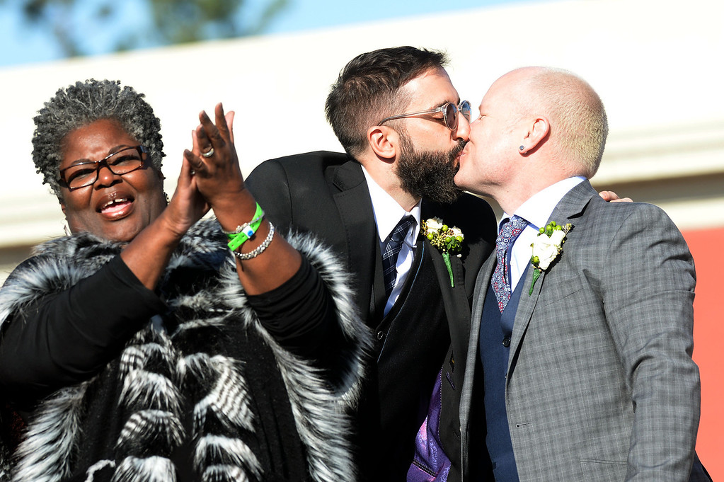 Description of . Rev. Alfreda Lanoix applauds as Danny Leclair and Aubrey Loots (l-r) kiss atop the AIDS Healthcare Foundation float during the 2014 Rose Parade in Pasadena, CA January 1, 2014. The couple was married during a same sex marriage on a cake-shaped float in the 125th Tournament of Roses Parade.2014 Rose Parade in Pasadena, CA January 1, 2014.(Keith Durflinger/San Gabriel Valley Tribune)