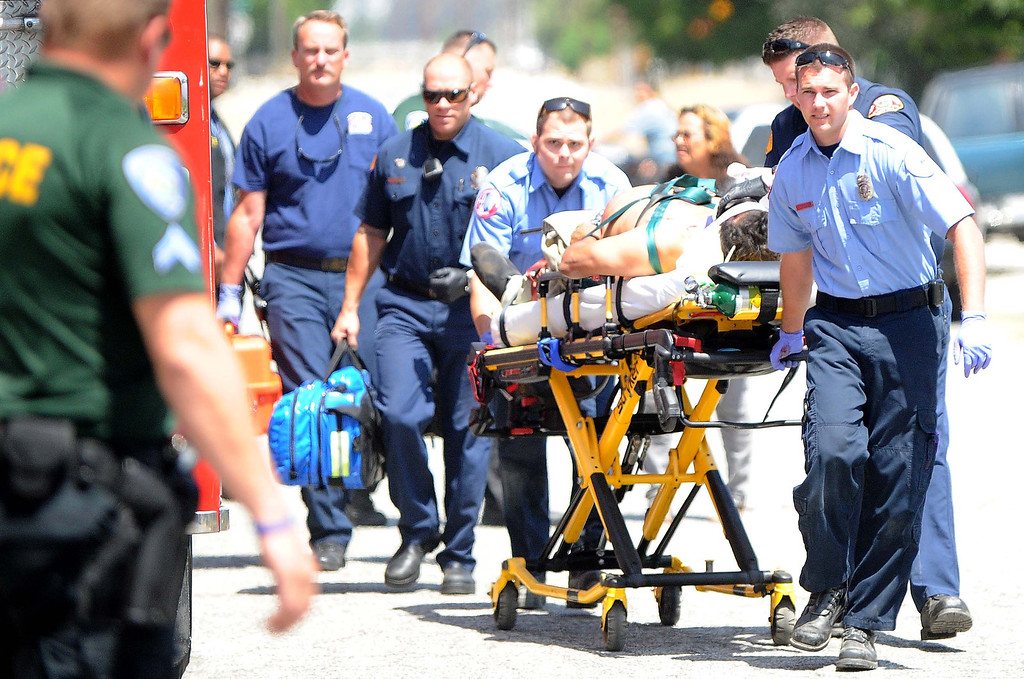 Description of . San Bernardino City Firefighters and paramedic rush a man to a hospital after he was shot in the head Thursday May 24,2013 in the 400 block of Norman Road in San Bernardino. (Lafonzo Carter/Staff Photographer)