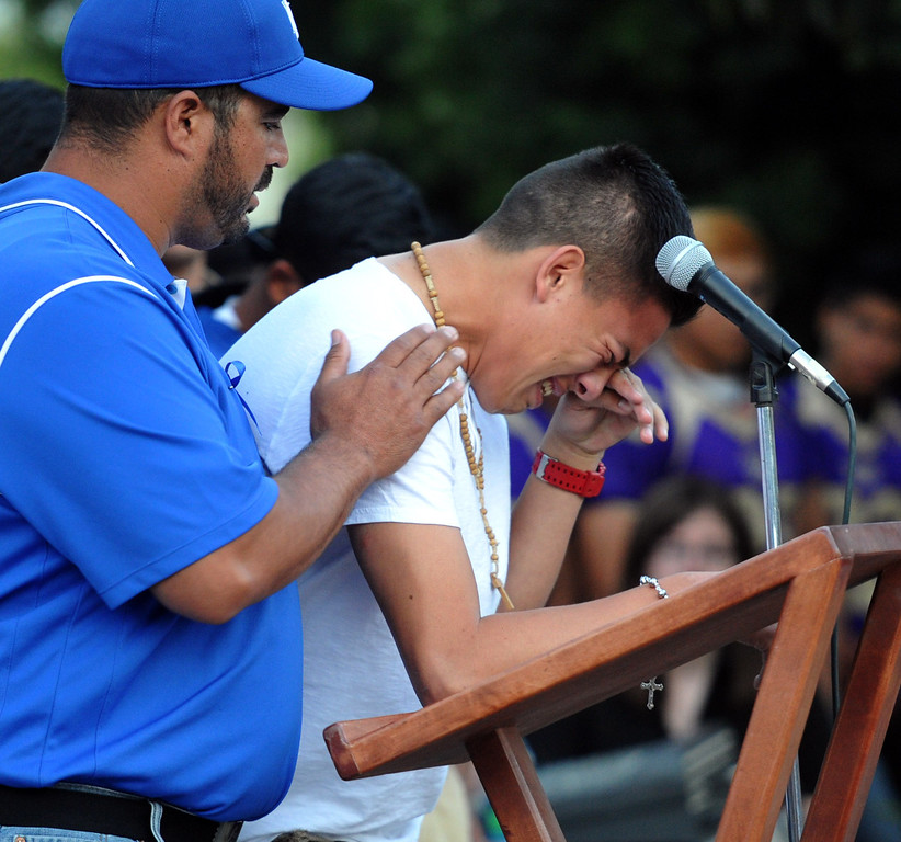 Description of . Football coach Joel Sanchez holds up a student who was on the bus when it crashed, cries as he tells the story as family, students and members of the community gather in memory of Adrian Castro, 19, at El Monte High School Monday evening April 14, 2014. Castro was one of nine students killed in the bus crash in Orland, Calif. (Staff Photo by Keith Durflinger/San Gabriel Valley Tribune)