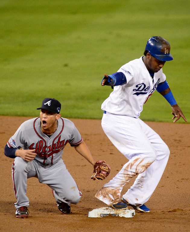 Description of . Atlanta Braves' Andrelton Simmons reacts as Los Angeles Dodgers' Hanley Ramirez steels second during the first inning in game 4 of the NLDS at Dodger Stadium Monday, October 7, 2013. (Photo by Sarah Reingewirtz/Los Angeles Daily News)
