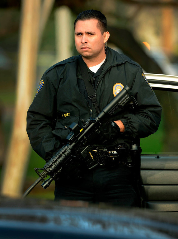 Description of . A Riverside Police officer stands watch at the intersection of Arlington and Magnolia Avenues in Riverside  where fugitive Christopher Dorner shot two Riverside officers killing one in Riverside February 7, 2012.  Arrests warrants for Christopher Dorner  have been released to the public by the County of Riverside. (Photo by Gabriel Luis Acosta/The Sun)
