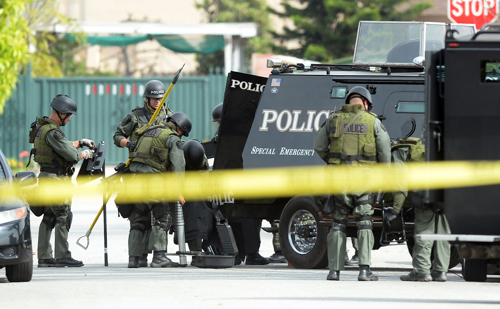 Description of . El Monte SWAT Team members stand down outside the home on the 11400-block of Elmcrest Street in El Monte after finding the suspect dead after a standoff on Friday March 7, 2014. The suspect shot his neighbor over a dispute Friday morning. (Photo by Keith Durflinger/San Gabriel Valley Tribune)