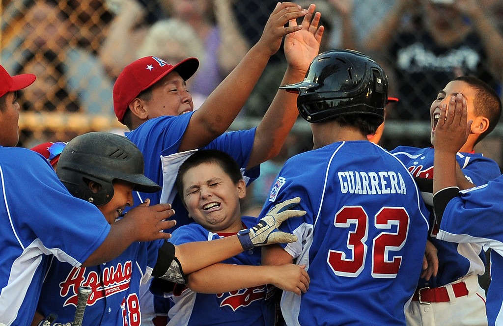 Description of . Azusa's Anthony Guarrera (32) mobbed by teammates after hitting a solo home run against  La Verne in the fourth inning of a championship Little League Section 3 championship baseball game at Homer Briggs Park on Wednesday, July 17, 2013 in Ontario, Calif. La Verne won 3-2 in 8 innings.   (Keith Birmingham/Pasadena Star-News)