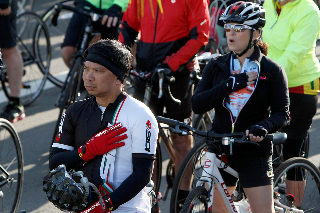 Description of . Participants of the R.U.F.F. Ride listen to the national anthem before the start of the ride during the Redlands Bicycle Classic on Saturday, April 5, 2014 in Redlands, Ca. (Photo by Micah Escamilla for the Redlands Daily Facts)