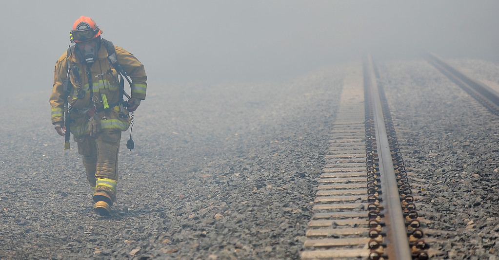 Description of . Los Angeles County firefighter capt. walks through heavy smoke as they battle 3-alarm fire at an abandoned warehouse near 9th Avenue and Clark Avenue on Tuesday, July 9, 2013 in City of Industry, Calif.  (Keith Birmingham/Pasadena Star-News)