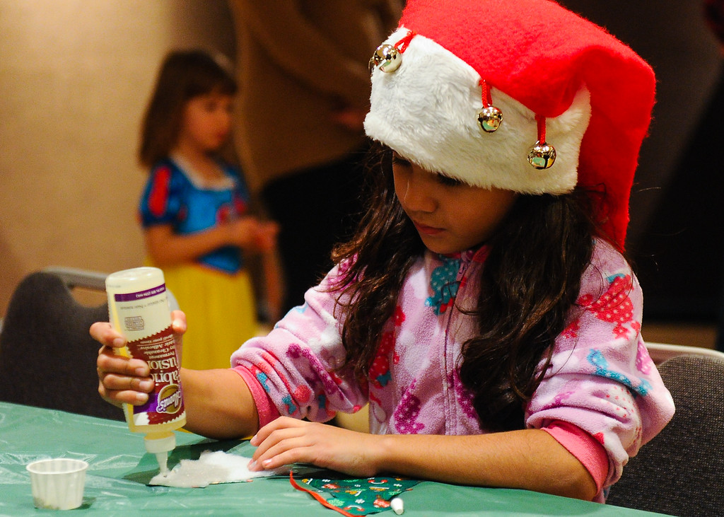 Description of . Franchesca (cq) Mercado, 8, makes holiday crafts during the annual Santa Pajama Party at the San Bernardino County Museum in Redlands on Friday, Dec. 6, 2013. (Photo by Rachel Luna / Redlands Daily Facts)