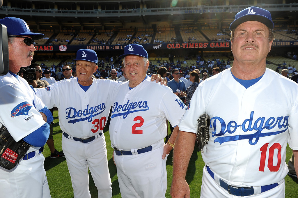 Description of . Former Los Angeles Dodgers manager Tommy Lasorda, right, with Maury Wills (30), Bill Buckner (22) and Ron Cey (10) during the Old-Timers game prior to a baseball game between the Atlanta Braves and the Los Angeles Dodgers on Saturday, June 8, 2013 in Los Angeles. 