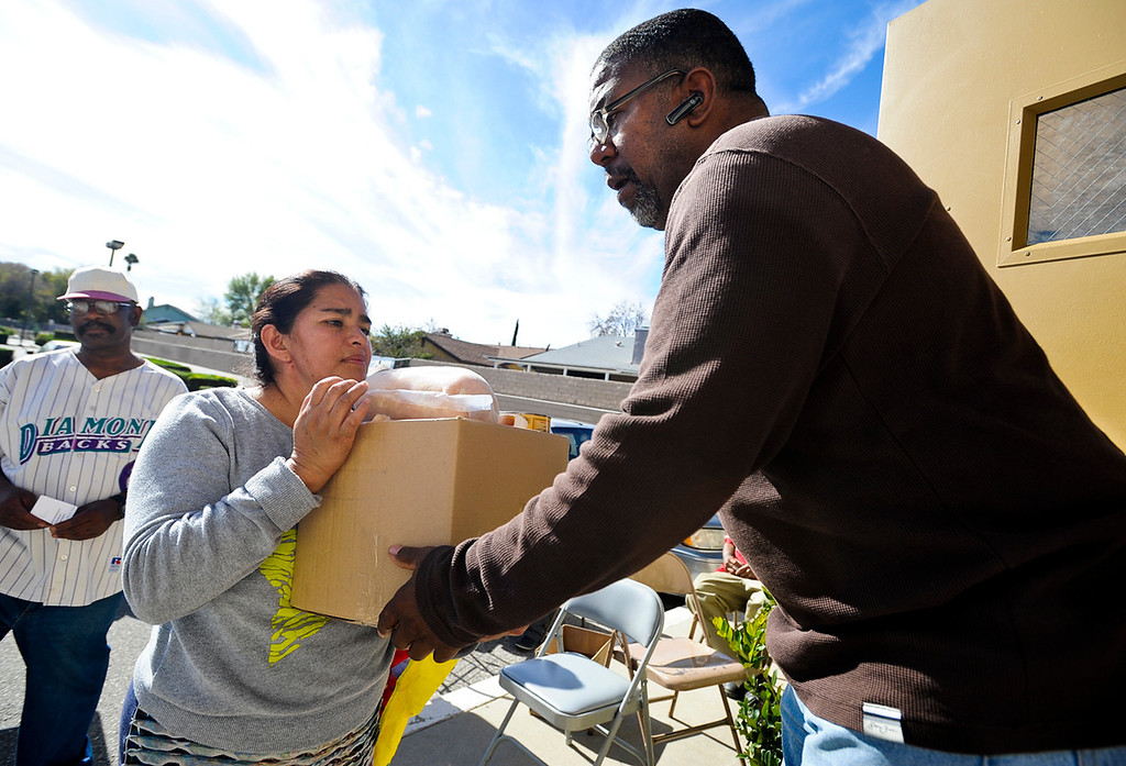 Description of . Volunteer Victor L. Woods gives Amelia Horrera a free Thanksgiving dinner basket given out at 16th Street Seventh-day Adventist Church in San Bernardino on Tuesday, Nov. 26, 2013. The church distributed 175 baskets to families-in-need. (Photo by Rachel Luna / San Bernardino Sun)