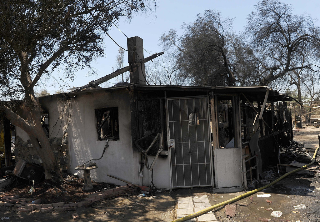 Description of . A vegetation fire in Jurupa Valley is 100 percent contained after destroying two homes and damaging two others.The Van Buren fire was kept to 12 acres nearly five hours after it started, said Scott Zisyak, a fire captain with Cal Fire.