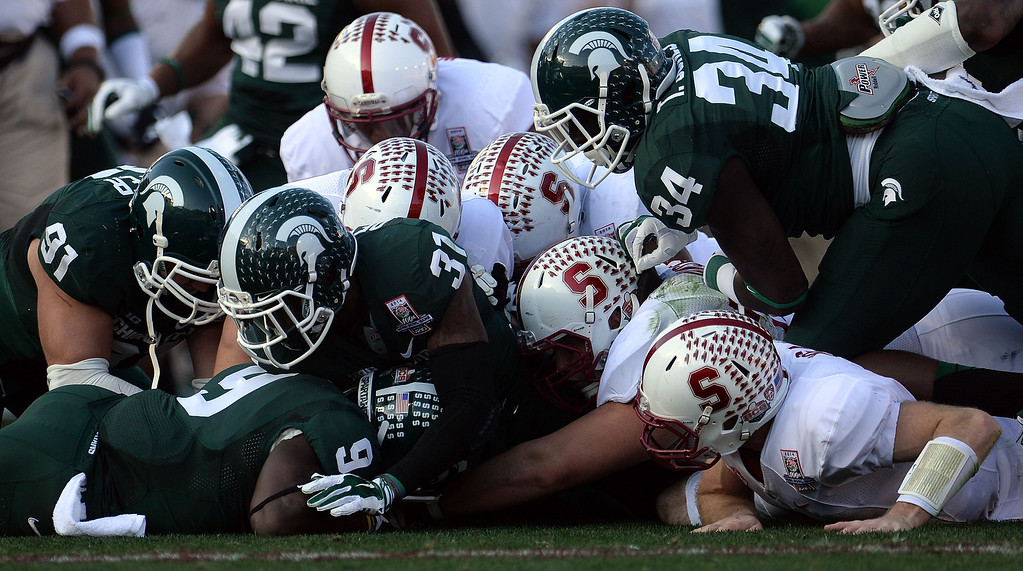 Description of . Stanford recovers their own fumble in the first half of the 100th Rose bowl game against Michigan State in Pasadena, Calif., on Wednesday, Jan.1, 2014. 