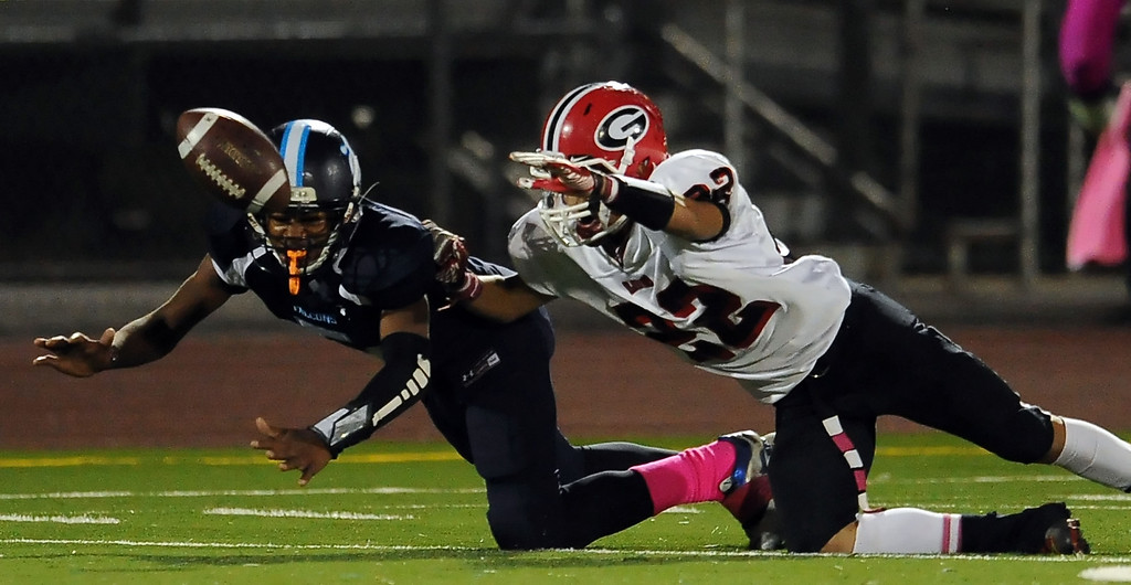Description of . Duarte's Darryl Robinson (5) knocks away a pass intended for Gladstone's Manny Mendez (22) in the first half of a prep football game at Duarte High School in Duarte, Calif., Thursday, Oct. 10, 2013.    (Keith Birmingham Pasadena Star-News)