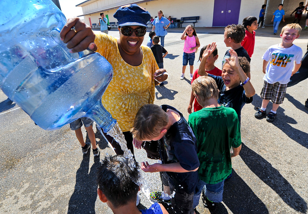 Description of . First grade teacher Nicole Williams pours bottled water on her students at the conclusion of a fun water activity on the final day of school at Hinkley School in Hinkley, Calif. on Thursday, June 6, 2013. Hinkley School is closing for good at the end of the 2012-2013 school year. (Rachel Luna / San Bernardino Sun)